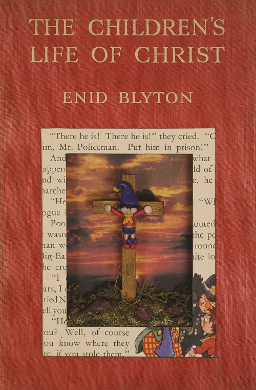A hard-case book titled The Children's Life of Christ by Enid Blyton. Inside the book the artist has the figurine of crucified Noddy, a clown with a pointy blue hat, short straight hair, red long-sleeve top, yellow scarf, blue shorts, and red shoes. The sky behind depicts a sad sunset.